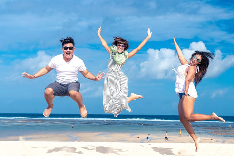three excited friends jumping on the beach