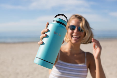 A woman holds up a blue insulated water bottle on the beach