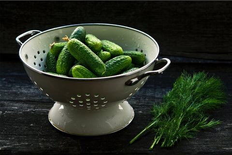 wet green small cucumbers in a strainer sitting on a counter
