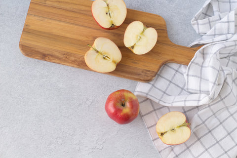 apples cut in half on a wooden cutting board