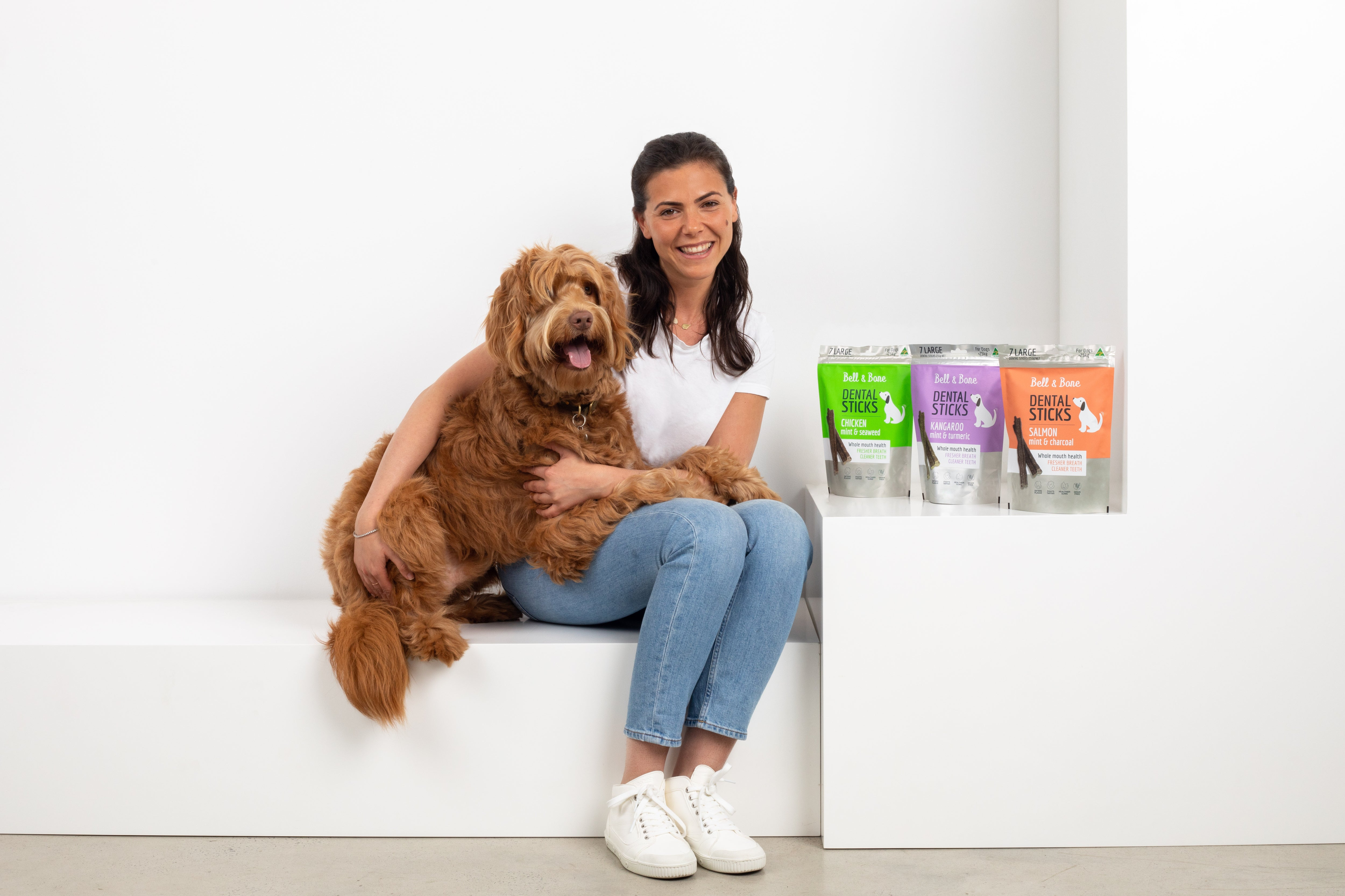 woman with a brown dog sitting next to 3 packs of Petzyo dental sticks