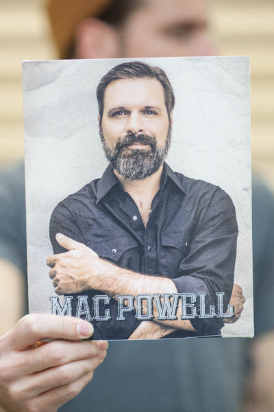 Model holding an 8x10 poster of a portrait Mac Powell crossing his arms.
