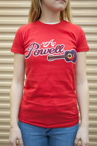 "A model wearing a red, ladies Mac Powell t-shirt that reads ""Mac Powell"" and has a design of a guitar."
