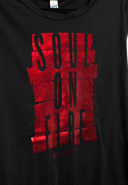 "Close up of a black Mac Powell ladies t-shirt with a shiny red design that reads ""Soul of Fire""."