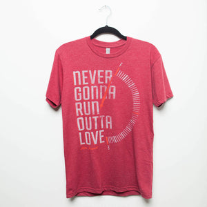 "A red Mac Powell t-shirt that reads ""Never Gonna Run Outta Love"" and has a design of a gas tank meter on full."