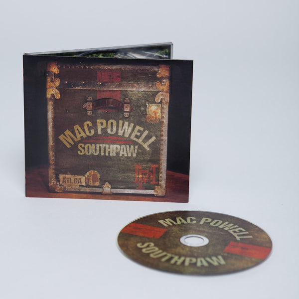 Mac Powell Southpaw CD that has a photo of a vintage chest on the cover displayed with the CD.