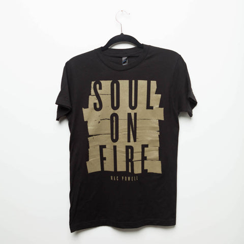 "A black Mac Powell t-shirt with a gold design that reads ""Soul of Fire""."