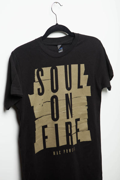 "Close up of a black Mac Powell t-shirt with a gold design that reads ""Soul of Fire""."