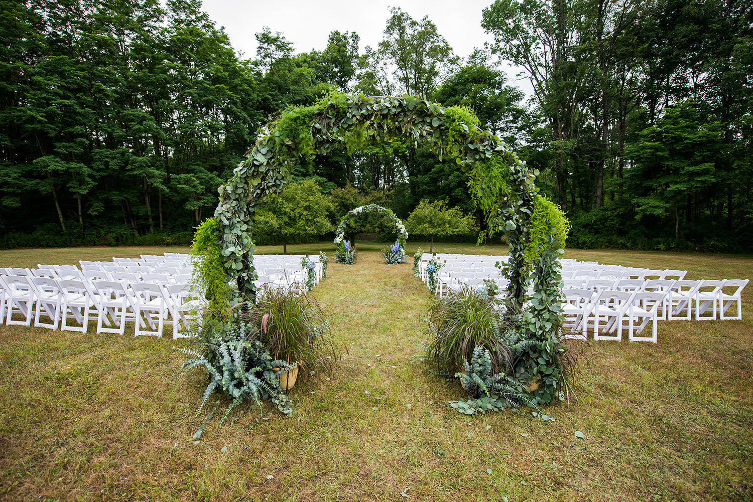 two moon arch wedding aisle in greens and blues