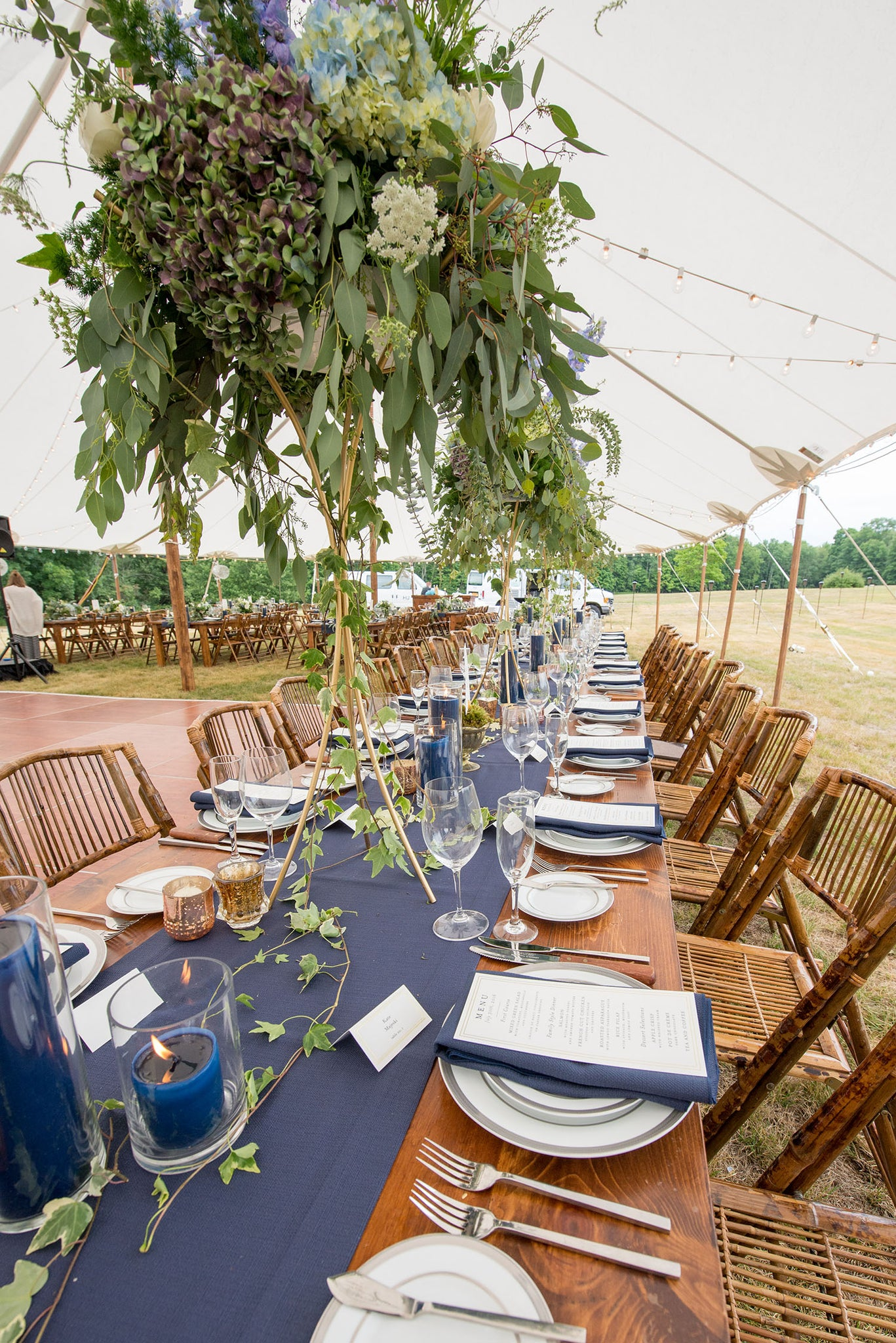 tall centerpiece on gold wire stand with navy blue pillar candles