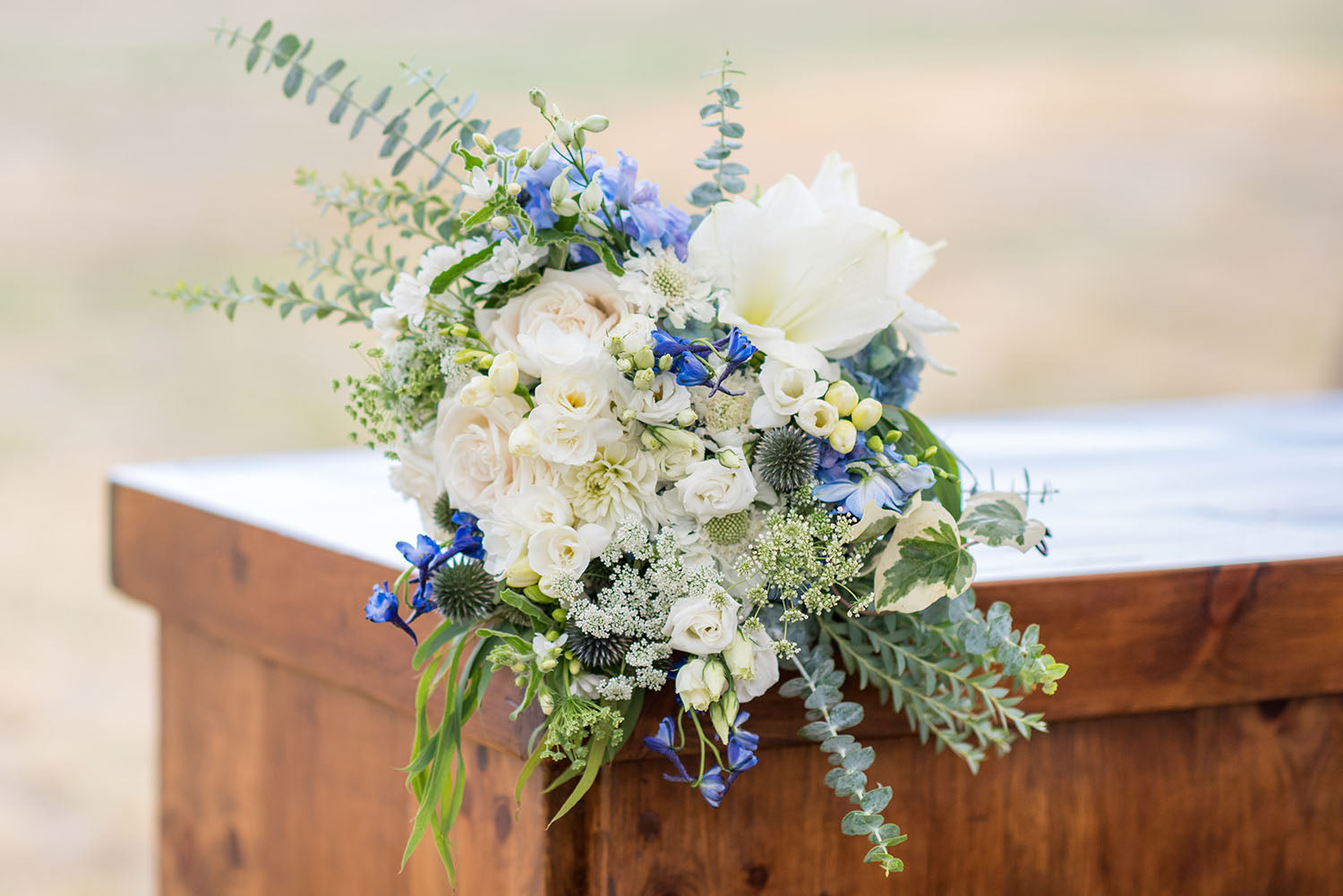 bridal bouquet in greens whites and blues with amaryllis and thistle