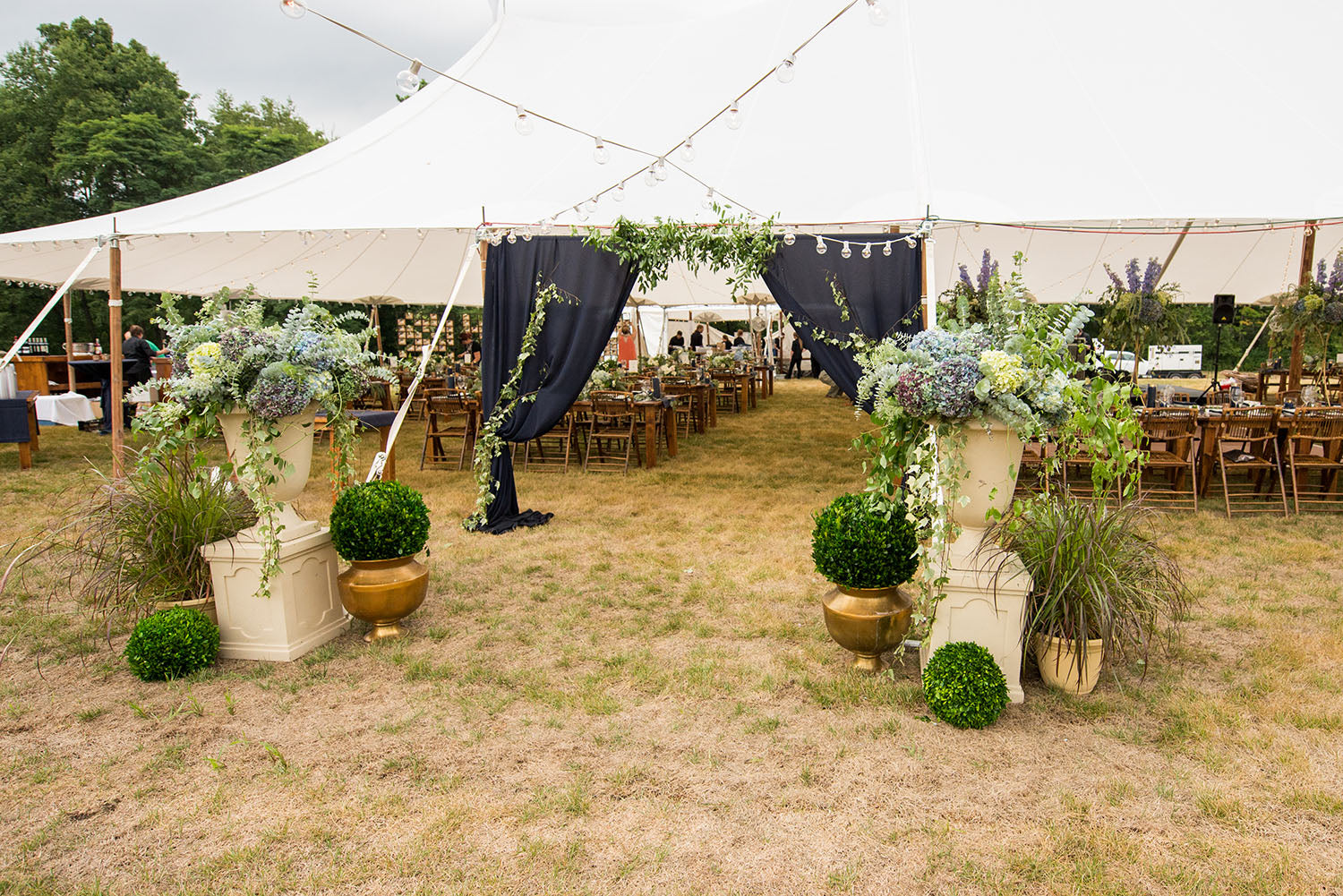 Wedding tent entrance with draped fabric and flowers
