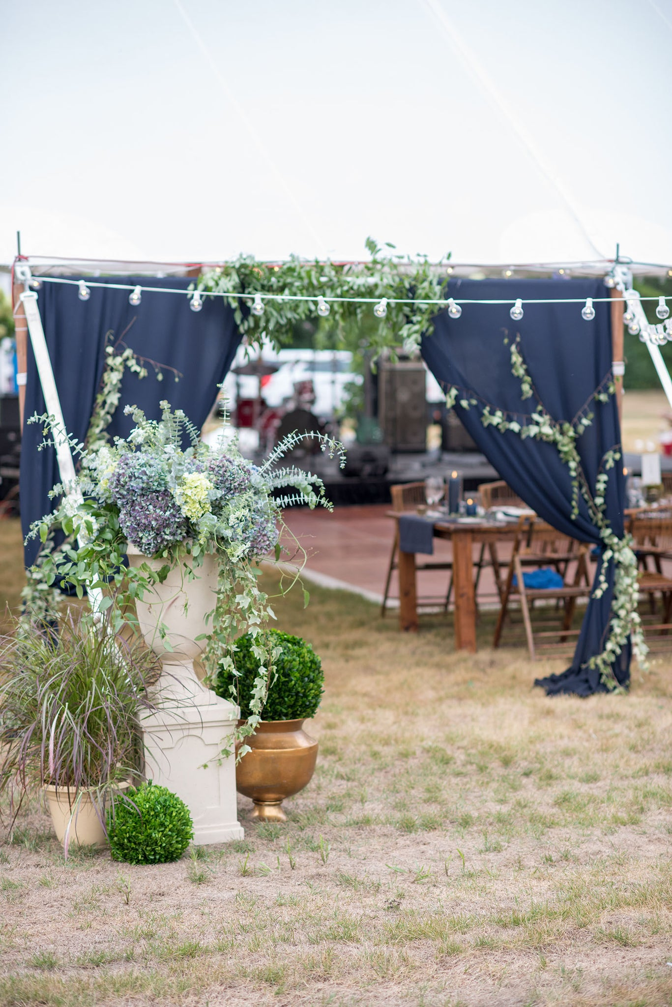 wedding tent entry with urns of flowers