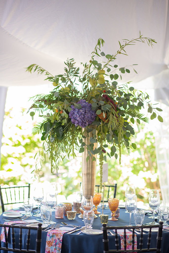 tall colorful centerpiece on gold vase