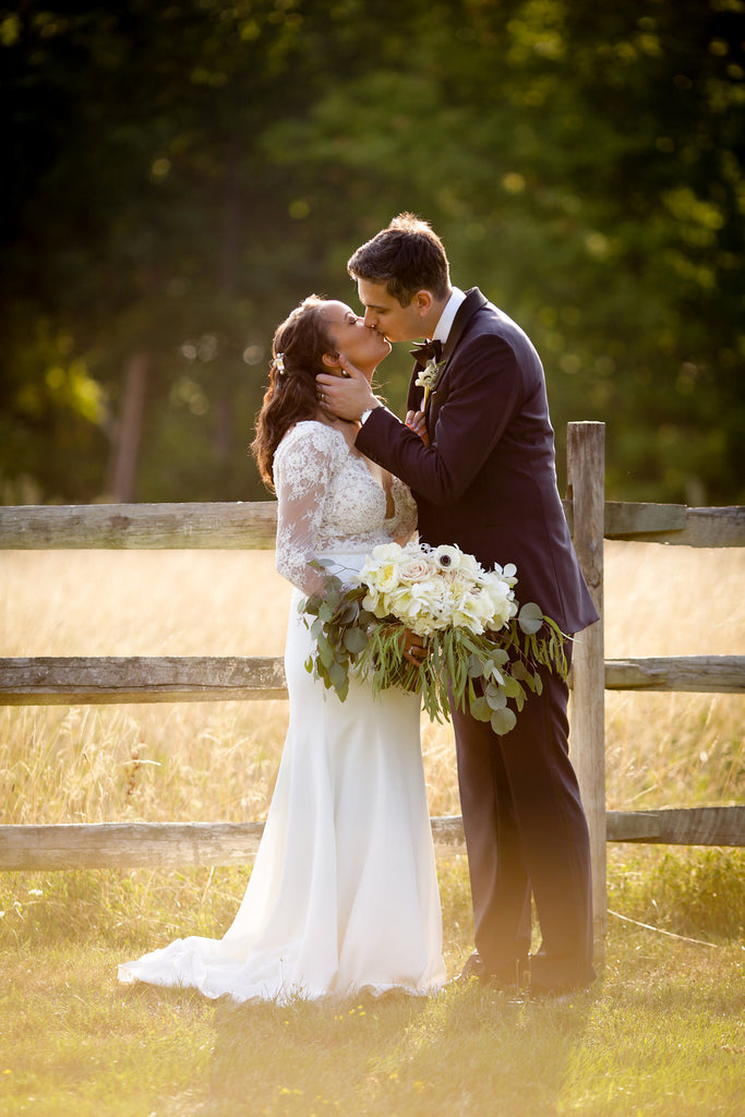 bride in lace dress with white and green bouquet