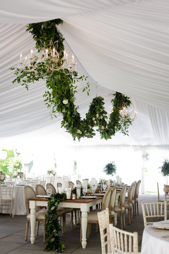 farm table head table with green garland and candles