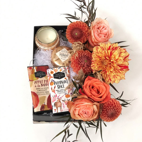 Stacy K Floral | Florist Rochester NY | The Fall Gift Box is filled with seasonal goodies. Seasonal flowers including colors orange, yellow, taupe, and red are paired with Seattle Chocolates Truffle Bars and a seasonal scented candle.