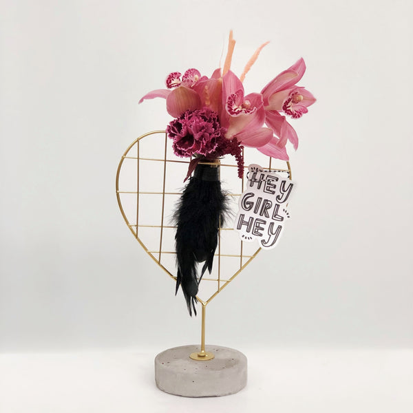 Stacy K Floral | Florist Rochester NY | Orchid blooms fill a heart-shaped vase stand with a feather detail. Arrangement comes with or without a vinyl sticker.