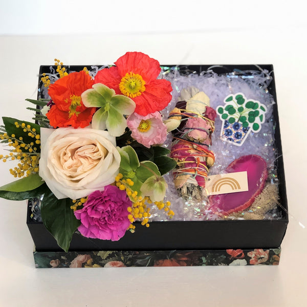 A colorful gift box featuring a fresh floral arrangement made of bold bright-colored flowers, Catherine Rising Floral Smudge Stick, geode slice, and a Cactus Club Paper Goods Plant Sticker