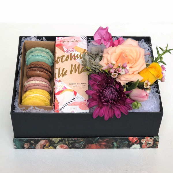 Black gift box with floral pattern lid contains a petite floral arrangement, five assorted French macarons from a local Rochester bakery, and Illume brand scented hand cream