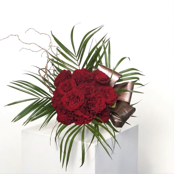 One dozen roses, beautifully arranged, and embellished with seasonal greenery. Wrapped presentation style. Can specify color in special instructions upon checkout.