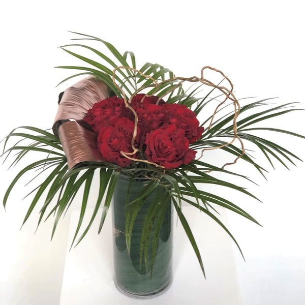Half dozen premium roses embellished with seasonal greenery in a clear cylinder vase. Specify color preference in special instructions upon checkout.