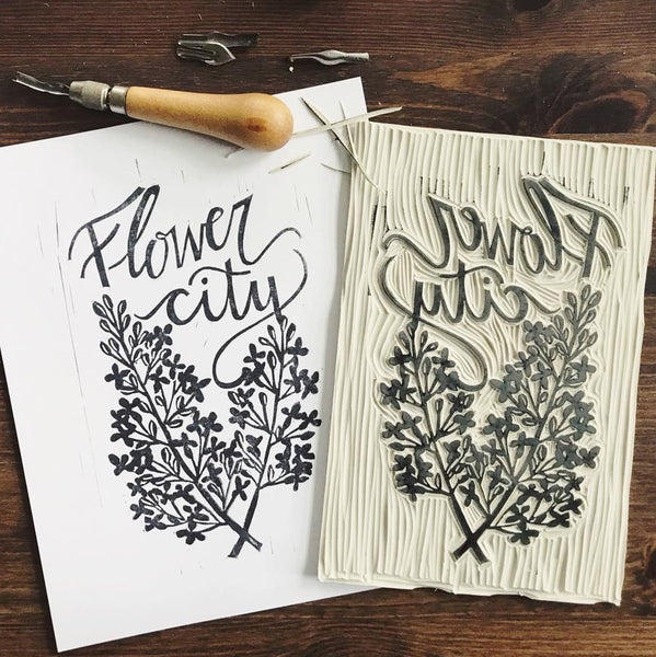 "Image of stamp with ink laying on top of a freshly stamped piece of paper; the print os an impression of a lilac and ""Flower City"" written above. We love local artists! This print is created from a stamp designed and carved by Kelsey of Ink & Pine Design. Stamped by hand, each print is one-of-a-kind and may vary from the images shown.   Fits frame size 8x10"