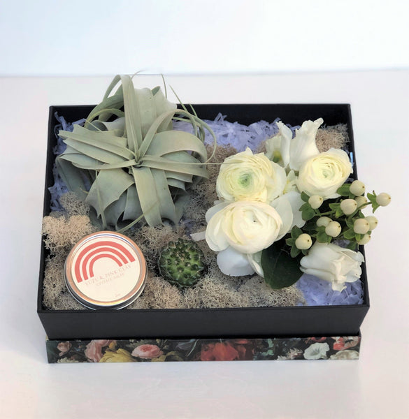 This gift box features a fresh floral arrangement in a neutral color palette, a xerographica air plant, mini cactus, Catherine Rising Upstate Salve, and reindeer moss for added texture
