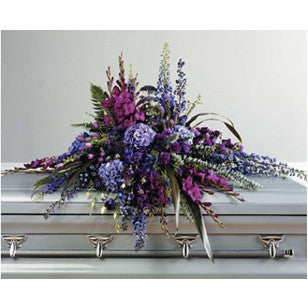 Casket spray of all shades of purple blooms.
