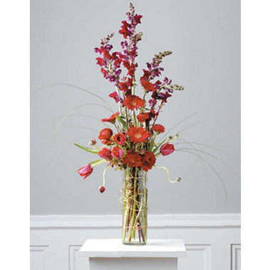 Rectangular vase filled with an assortment of red blooms designed tall and one sided.