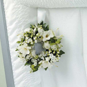 White and green wreath to hang inside the casket of freesia and other white blooms.