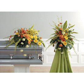 Tropical inspired sympathy suite including a spray and casket piece.