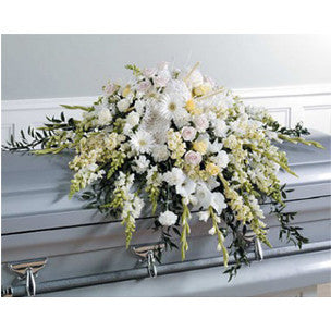 All white casket spray accented by subtle hints of soft yellow.