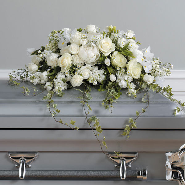 This casket spray is a collection of assorted white blooms including hydrangea, snap dragons, dahlias, and other seasonal blooms, with trailing ivy.