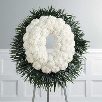 Sympathy wreath of white mums with an outer rim of green palms.