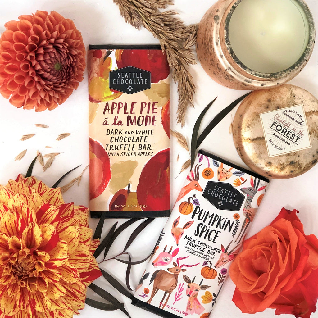 Stacy K Floral | Florist Rochester NY | The Fall Gift Box is filled with seasonal goodies. Seasonal flowers in warm fall colors are paired with Seattle Chocolates Truffle Bars and a seasonal scented candle.