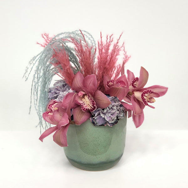 Stacy K Floral | Florist Rochester NY | The Pink and Teal Arrangement brings a unique style for Fall with orchid blooms and blooms to compliment. Dyed grasses add texture and dimension to this stylish arrangement.