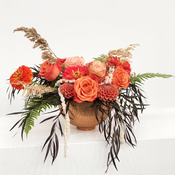 Stacy K Floral | Florist Rochester NY | A striking copper bowl with a delicately etched pattern is the perfect vessel for this bloom-filled design. Fall Floral in Copper Bowl is designed with fresh flowers in rich oranges and red with seasonal greens to create an abundant fall design.  Substitutions will be made based on availability.