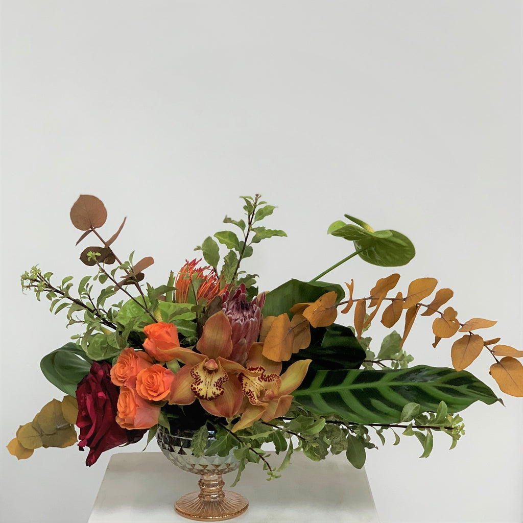 fall centerpiece with protea and roses