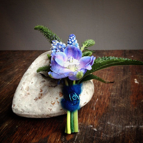 Blue delphinium boutonniere with accents of grape hyacinth, blue wool, and wire embellishments.