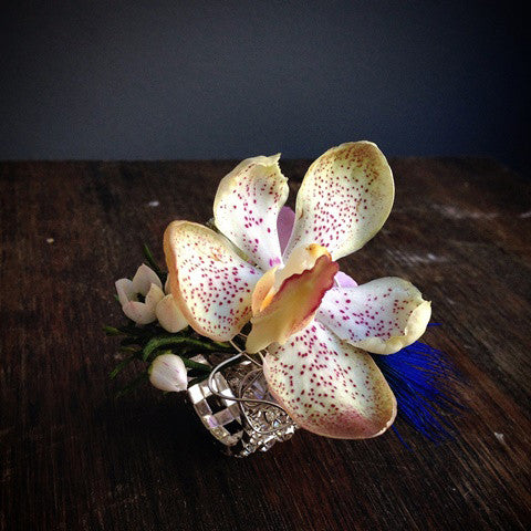 The Orchid flower ring is constructed of an orchid blossom, with feather accents placed atop a rhinestone ring.