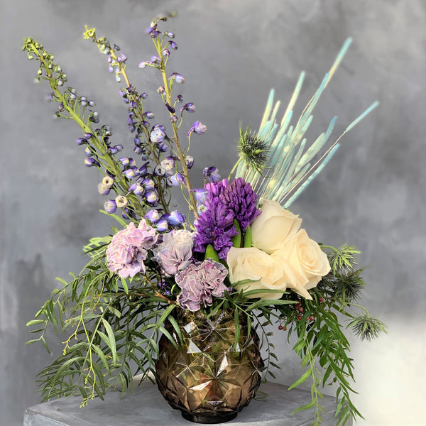 purple vase with blue and purple flowers