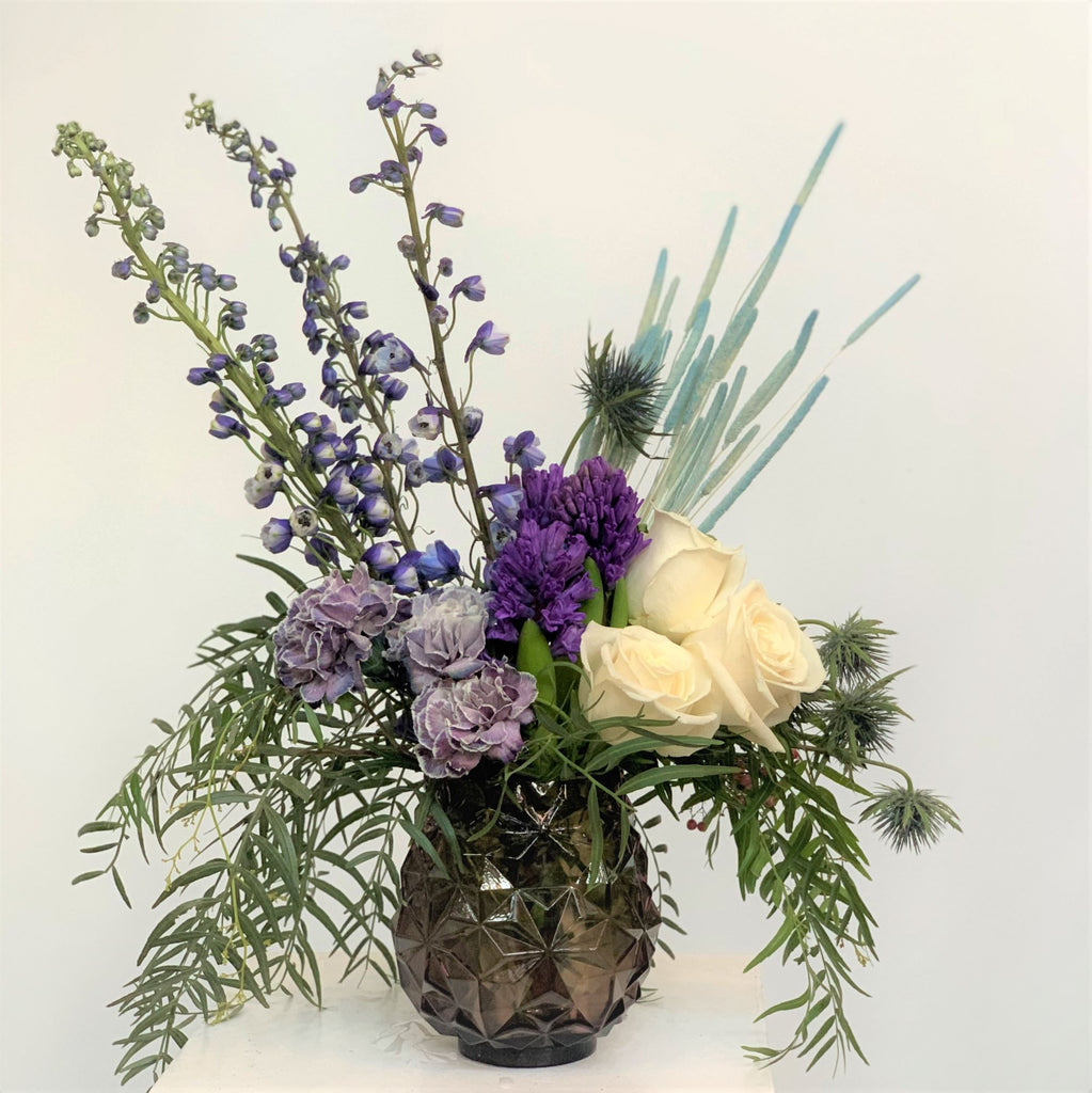 Purple vase with carnations, roses, delphinium