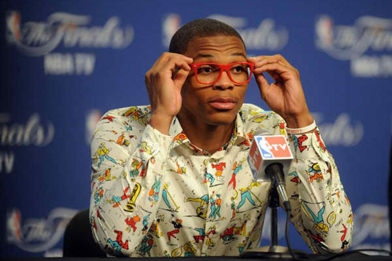 Russell Westbrook in a media scrum wearing a Prada shirt.