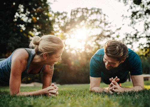A pair of fitness enthusiasts planking in a peaceful park
