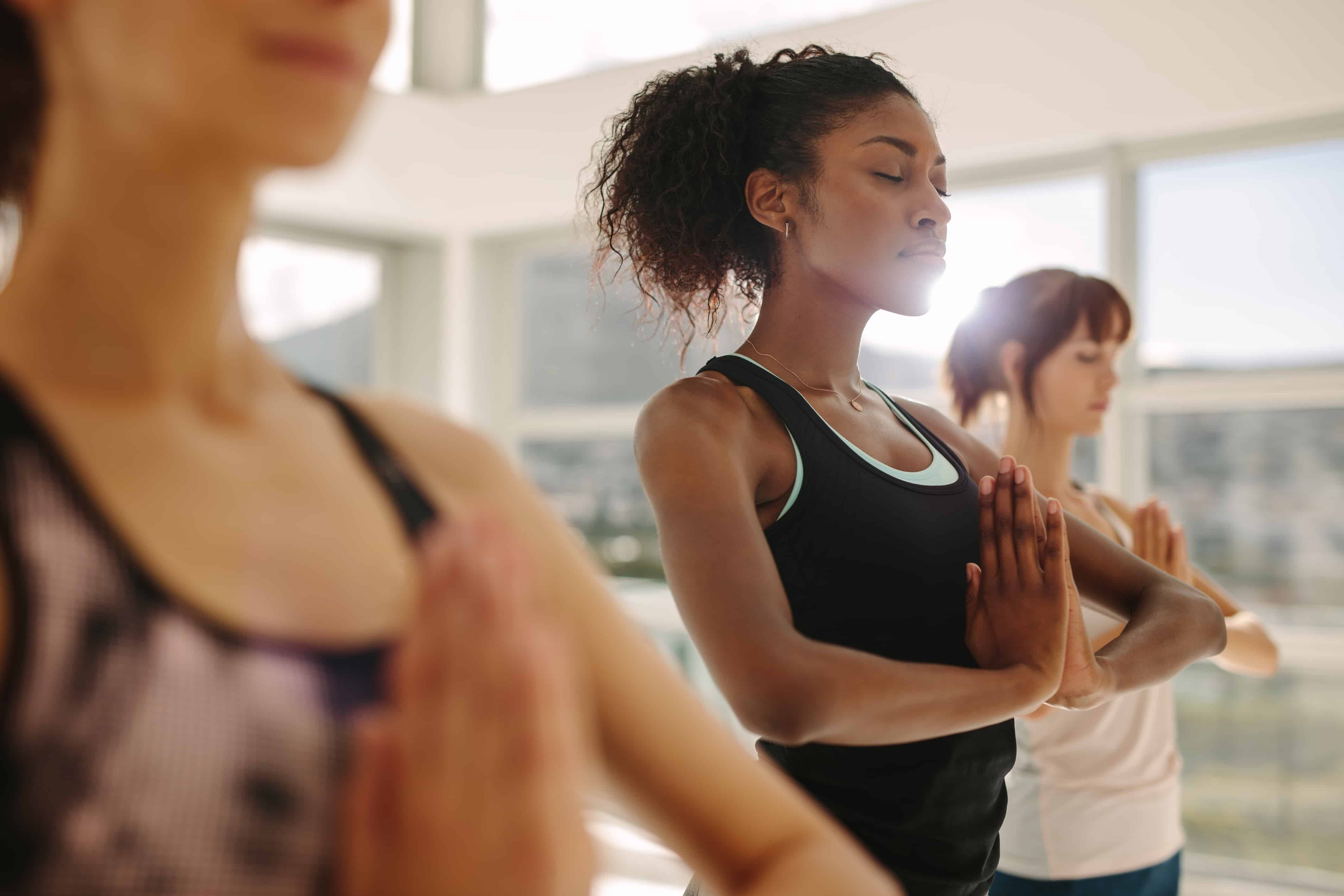 Women practicing mindful meditation in a yoga class
