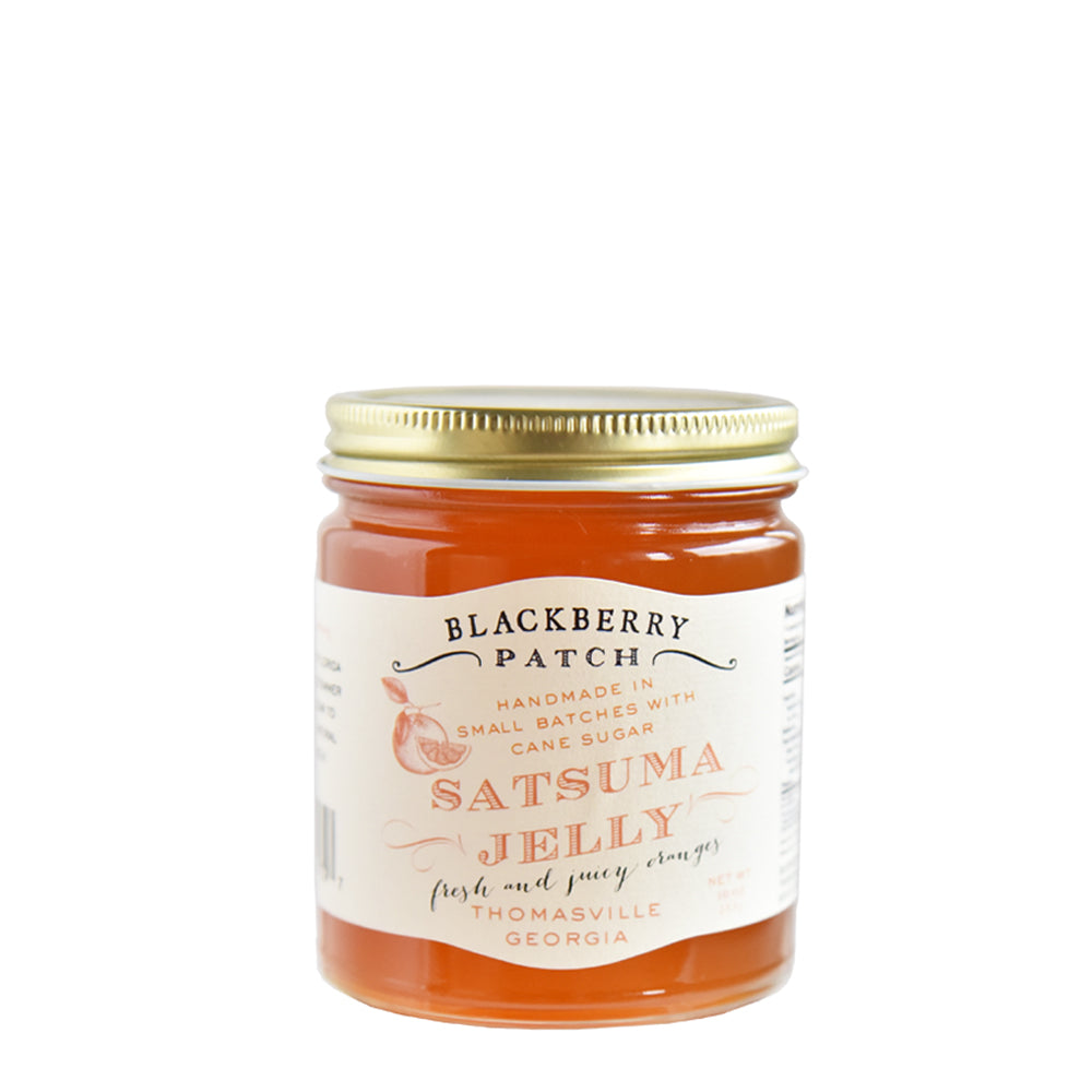 10oz glass jar of Blackberry Patch Satsuma Jelly with gold screw on lid.