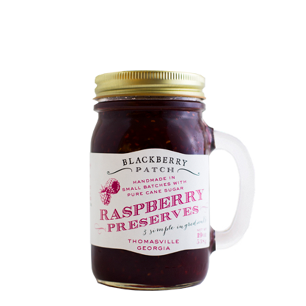 19oz jar of Blackberry Patch Raspberry Preserves. Jar is a handled mug with gold screw top.