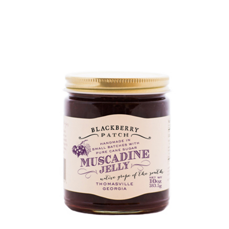 10oz jar of Blackberry Patch Muscadine Jelly with gold screw on lid.