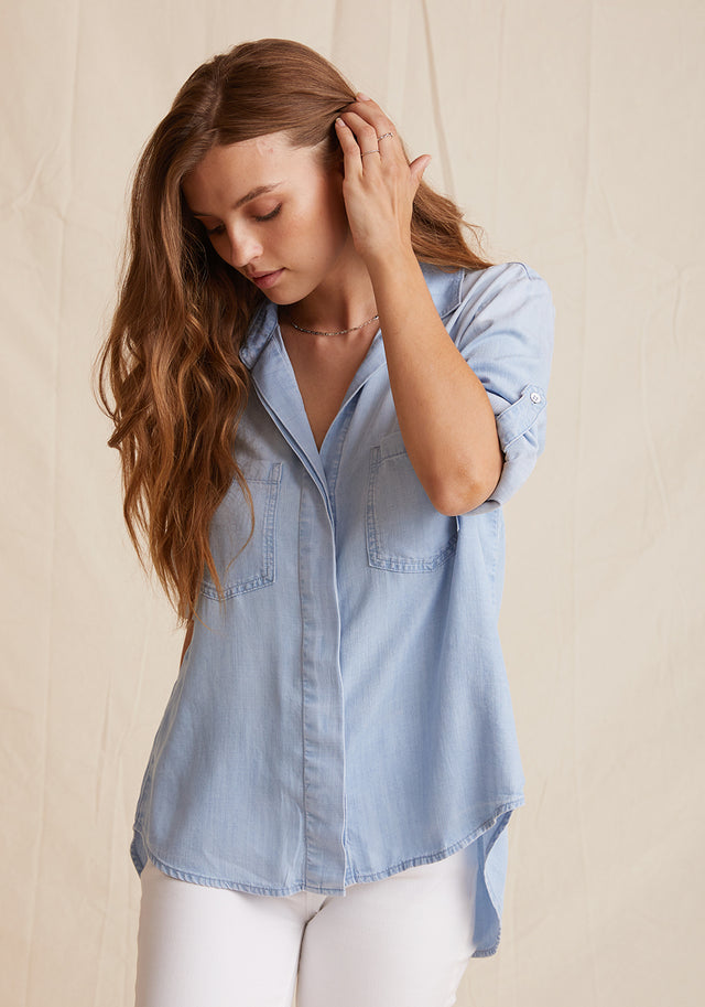 Front View: Womens Light Denim Wash Long Sleeve Button Down Shirt With Front Pockets and Collared Neckline